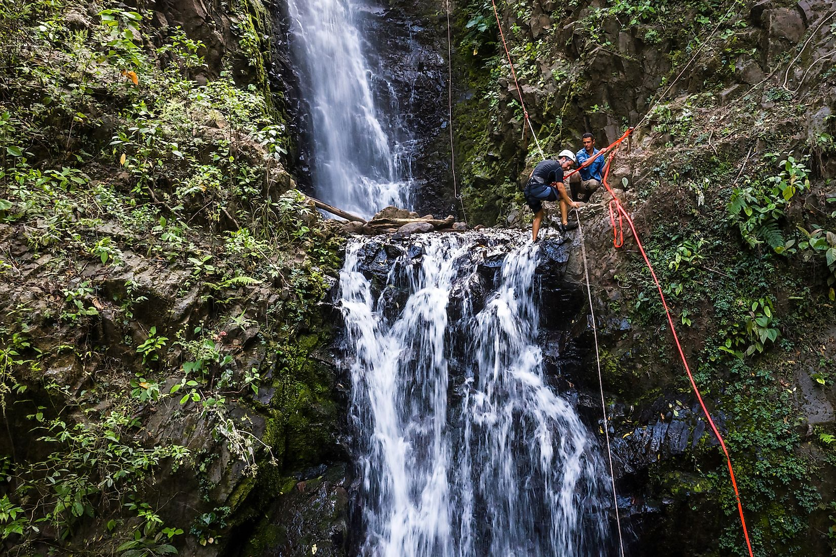 Adventure tourism in tropical Costa Rica while rappelling down a beautiful waterfall deep in the southern mountains of the country. Image credit: Wollertz/Shutterstock.com