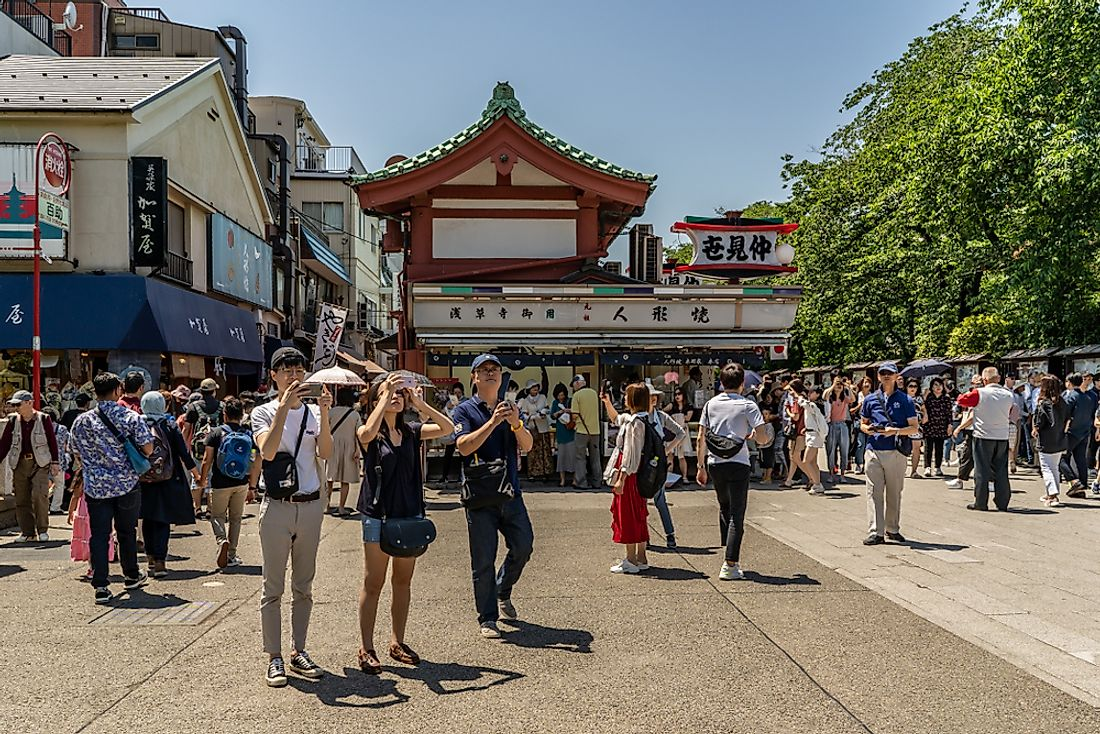 Tourists explore Tokyo, Japan. Editorial credit: Page Light Studios / Shutterstock.com.