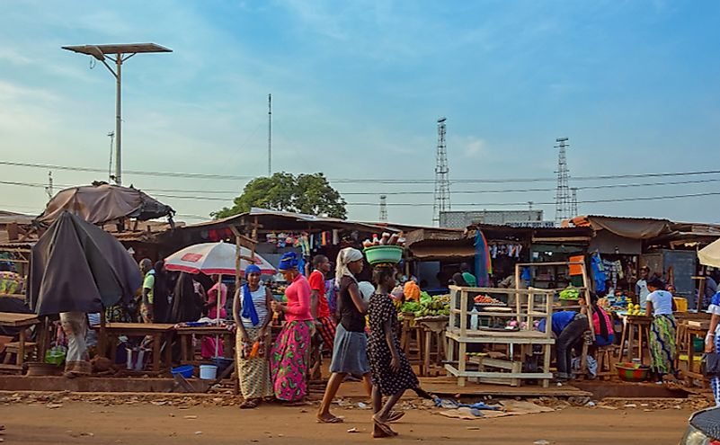 Street scene with the buyers, vendors selling their goods in a street market in the outskirt of Conakry city.