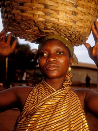 Woman Wearing Gold Fabric Dress and Carrying Basket, Kabile, Brong-Ahafo Region, Ghana