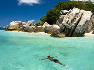 Local Man Swimming at the Granite Rocks at Ile Aux Cocos, Seychelles, Indian Ocean, Africa