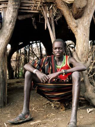Karamojong Boy Sitting at Entrance to Hut, Uganda