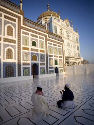 Men Kneel in the Courtyard of a Sufi Shrine in Pir Pagoro, Pakistan