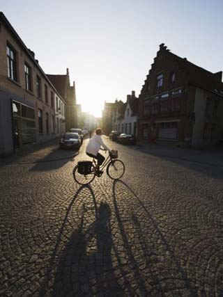 Sunset and Shadow of a Cyclist on Cobbled Street, Old Town, UNESCO World Heritage Site, Bruges