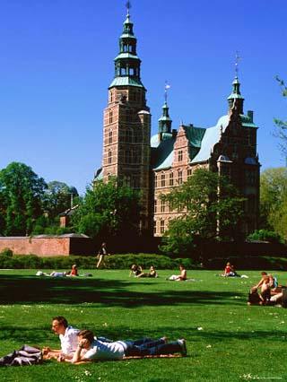 People Relaxing on Lawn with Rosenborg Slot Castle in Background, Copenhagen, Denmark