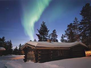 Aurora Borealis over Log Cottages in Arctic Finland