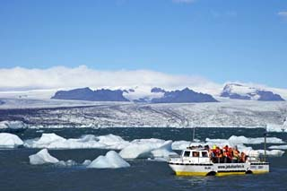 Amphibious Vehicle Between Icebergs on Glacial Lake at Jokulsarlon with Vatnajokull Icecap, Iceland