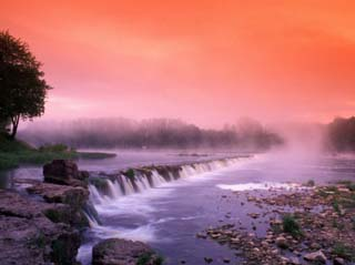 Sunrise in the morning mist over the waterfall on the Venta River near Kuldiga, Latvia