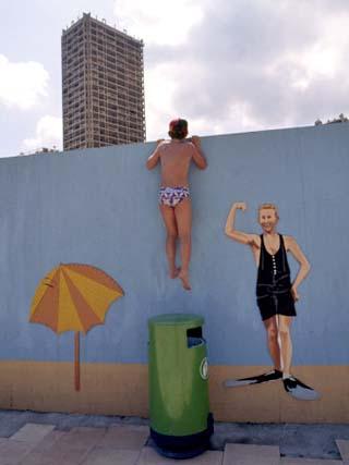 A Boy Peeking over Wall of a Hotel Swimming Pool in Monaco
