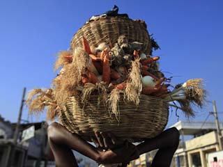 Woman Carries Baskets with Vegetables from a Street Market in Downtown Port-Au-Prince