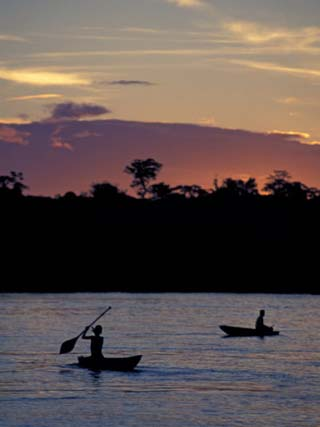 Boaters on Amazon River at Sunset, Amazon River Basin, Peru